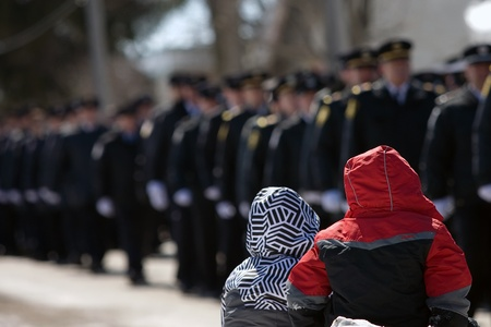 converged: March 24, 2011. Listowel, Ontario. Two young children watch as a procession of firefighters walk past them. Thousands of firefighters from Ontario, Quebec and the United States converged on Listowel to honour volunteer firefighters Ken Rae 56 and Raymond