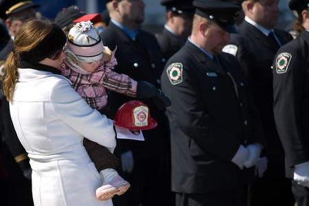 converged: March 24, 2011. Listowel, Ontario. Alyssa Beirnes and her mom Tammy Beirnes stand and watch as a the procession of firefighters stops in front of them. Thousands of firefighters from Ontario, Quebec and the United States converged on Listowel to honour vo