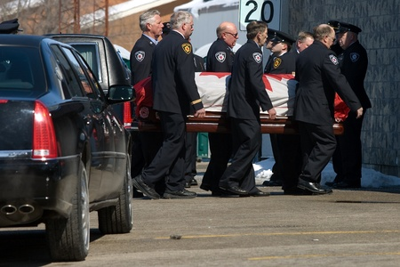 converged: March 24, 2011. Listowel, Ontario. Drapped in the Canadian flag, the casket of Raymond Walter is carried into the Listowel Community Arena for a private funeral service. Thousands of firefighters from Ontario, Quebec and the United States converged on Lis Editorial