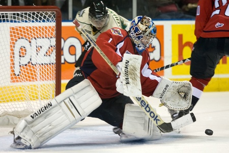 London Ontario, Canada - October 7, 2011. Windsor Spitfire goalie and Dallas Star draft pick Jack Campbell moves to smother the puck while London Knight forward Andreas Athanasiou moves in. Windsor won the game 5 - 2.