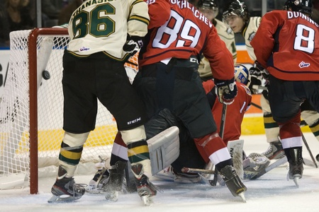 eventually: London Ontario, Canada - October 7, 2011. London Knights and Windsor Spitfire players crash the Spitfire net eventually getting the puck past Spitfire goalie Jack Campbell.