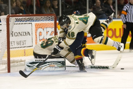 john labatt centre: London Ontario, Canada - October 14, 2011. London Knight Matt Rupert jumps to avoid his goalie, Micheal Houser and an Erie Otter player during their game against the Erie Otters. London won the game 6-4
