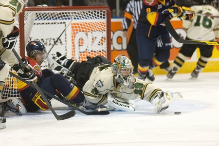 London Ontario, Canada - October 14, 2011. London Knight goalie Micheal Houser stretches to make hand pass to a fellow player in their game against the Erie Otters. London won the game 6-4.  Stock Photo - 10911437