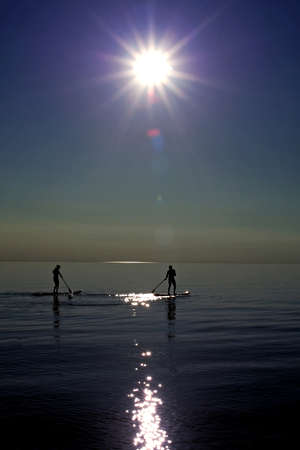 huron: Bayfield Ontario, Canada - July 20, 2010. Two individuals paddle out onto Lake Huron just before sunset.