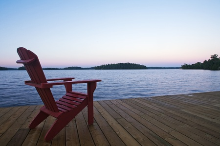 June 1, 2011. A Muskoka chair on a dock at a lakeside resort in Muskoka Ontario Canada.  photo