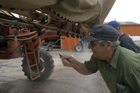 Parkhill Ontario, Canada - May 5, 2008. Simon Willemse inspects the nozzels on his crop sprayer.