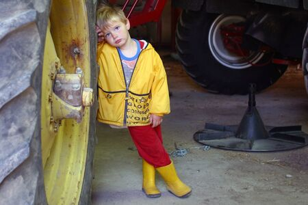 Parkhill Ontario, Canada - September 21, 2006. A young farm boy leans against the wheel of a large tractor.
