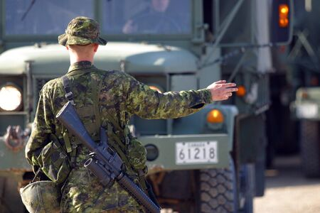 canadian military: Meaford Ontario Canada. May 11, 2008. A Canadian soldier directs a transport vehicle during pre-deployment exercises.