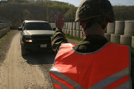 Meaford Ontario Canada. May 11, 2008. A Canadian soldier motions to halt an army truck from entering a Forward Operating Base during the Canadian Forces predeployment training called Maple Storm Two.