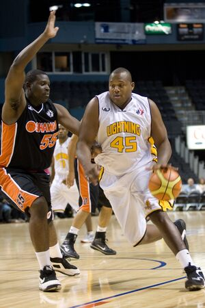 London Ontario, Canada - October 23, 2011. Shawn Daniels (45) drives to the net against Hugh Barnett (55) of the Oshawa Power during their National Basketball League of Canada game. London won the game 111-83.