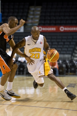 London Ontario, Canada - October 23, 2011. Eddie Smith (20) of the London Lightning drives past Josh Porter (1) of the Oshawa Power during the National Basketball League of Canada game. London won the game 111-83.  Editorial