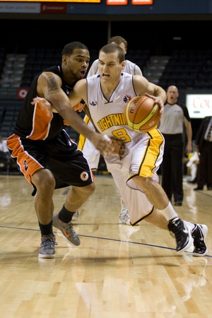 London Ontario, Canada - October 23, 2011. Nick Lother (8) of the London Lightning drives past Larry Diamond (2) of the Oshawa Power during their National Basketball League of Canada game. London won the game 111-83.  Editorial