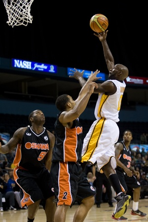 2 50: London Ontario, Canada - October 23, 2011. DeAnthony Bowden of the London Lightning goes up for basket against Oshawa Power players Larry Diamond (2) and Jushay Rocket (50) during their National Basketball League of Canada game. London won the game 111-83
