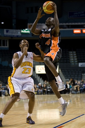 London Ontario, Canada - October 23, 2011. Tut Ruach of the Oshawa Power goes up for a basket against Tim Ellis (23) of the London Lightning during a National Basketball League of Canada game. London won the game 111-83.