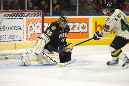 maxwell: London Ontario, Canada - October 30, 2011. Matt Rupert (46) of the London Knights gets the puck past Brandon Maxwell (45) of the Sarnia Sting during a shootout. London won the game 3-2.