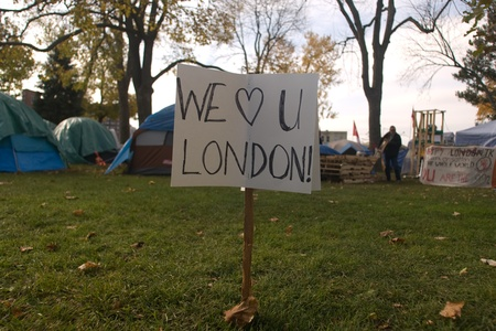approached: London Ontario, Canada - November 8, 2011. The Occupy London encampment in Victoria Park woke to notices posted around their camp to vacate the park by 6pm.  As 6pm approached protestors moved resources to a singular tent where they later surrounded by li Editorial