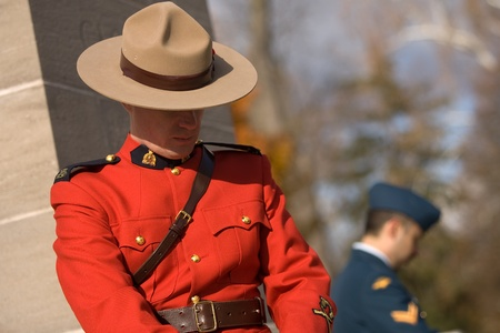 victoria park: London Ontario, Canada - November 11, 2011. An RCMP officer and Canadian Airman stand posts during Remembrance Day ceremonies at the Cenotaph in Victoria Park in London Ontario Canada.  Editorial