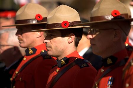 London Ontario, Canada - November 11, 2011. RCMP officers with poppies in their signature stetsons during Remembrance Day ceremonies at the Cenotaph in Victoria Park in London Ontario Canada.