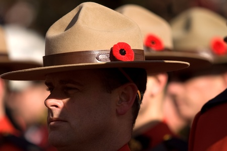 London Ontario, Canada - November 11, 2011. RCMP Officers with Poppies in their signature Stetson headgear during Remembrance Day ceremonies at the Cenotaph in Victoria Park in London Ontario Canada.