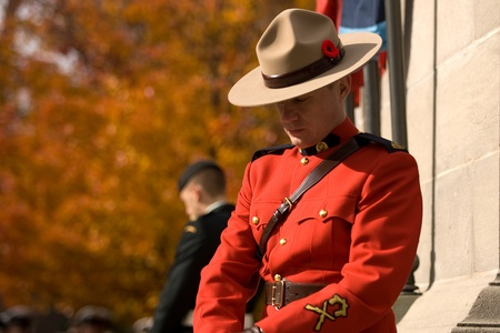 victoria park: London Ontario, Canada - November 11, 2011. A Royal Canadian Mounted Police Officer stands a post during Remembrance Day ceremonies at the Cenotaph in Victoria Park in London Ontario Canada.  Editorial