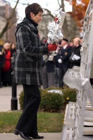 victoria park: London Ontario, Canada - November 11, 2011. Carolyn Wilson, mother of deceased Royal Dragoon Trooper Mark Wilson lays the ceremonial Silver Cross during Remembrance Day ceremonies at the Cenotaph in Victoria Park in London Ontario Canada.  Editorial