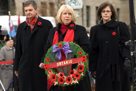 London Ontario, Canada - November 11, 2011. From left to right, Ontario Liberals Chris Bentley and Deb Matthews are joined by Ontario NDP member Teresa Armstrong as they prepare to lay a wreath during Remembrance Day ceremonies at the Cenotaph in Victori