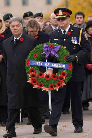London Ontario, Canada - November 11, 2011. Joe Fontana, Mayor of London, left and Brad Duncan, Chief of Police for City of London prepare to lay a wreath during Remembrance Day ceremonies at the Cenotaph in Victoria Park in London Ontario Canada.