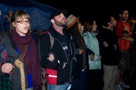 vacate: London Ontario, Canada - November 8, 2011. The Occupy London encampment in Victoria Park woke to notices posted around their camp to vacate the park by 6pm.  As 6pm approached the protestors and supporters linked arms and encircled their Library tent by