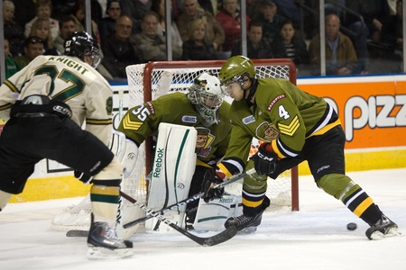 third eye: London Ontario, Canada - November 4, 2011. Brampton Battalion goalie Matej Machovsky keeps on eye on a pass made by Jared Knight (97) that gets past Marcus McIvor (4).  London won the game 3-2 scoring the winning goal in the last minute of the third perio