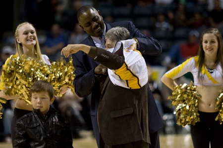 London Ontario, Canada - November 4, 2011. Joe Fontana, Mayor of London Ontario, has a slight wardrobe malfunction as he tries to put on a London Lightning jersey. Lightning coach Michael Ray Richardson who eventually came to the Mayor's aid.  London won  Stock Photo - 11355452