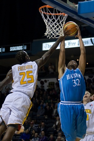 London Ontario, Canada - November 4, 2011. Gabe Freeman (25) of the London Lightning goes up to block a shot from Shawn Hawkins (32) of the Halifax Rainmen. London won the game 118-110 in front a crowd of 3600 spectators. Stock Photo - 11355460
