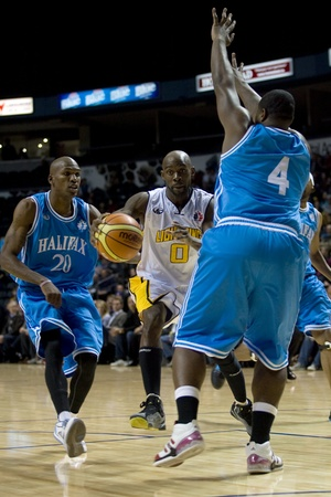 london lightning: London Ontario, Canada - November 4, 2011. DeAnthony Bowden (0) of the London Lightning drives between Halifax Rainmen Eric Crookshank (20) and DeAndre Thomas (4) during their game.  London won the game 118-110 in front a crowd of 3600 spectators.