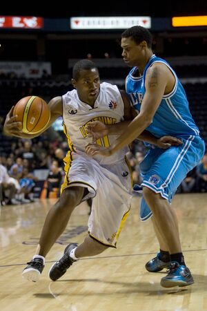 London Ontario, Canada - November 4, 2011. Brandon Dean of the London Lightning drives around a Halifax Rainmen player during their game. London won the game 118-110 in front a crowd of 3600 spectators.