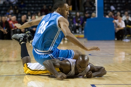 London Ontario, Canada - November 4, 2011. Darrin Dorsey (28) of the Halifax Rainmen falls on DeAnthony Bowden of the London Lightning during their game. London won the game 118-110 in front a crowd of 3600 spectators.