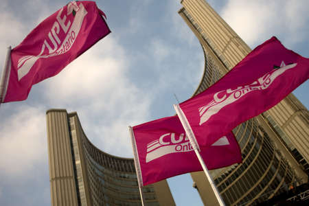 99: Toronto Ontario, Canada - November 24, 2011. Canadian Union of Public Employee also known as Cupe flags held by protestors fly outside of the Toronto City Hall at Nathan Phillips Square during a Ontario Federation of Labour of rally against the practices