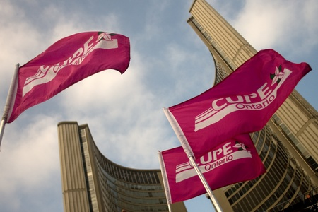 Toronto Ontario, Canada - November 24, 2011. Canadian Union of Public Employee also known as Cupe flags held by protestors fly outside of the Toronto City Hall at Nathan Phillips Square during a Ontario Federation of Labour of rally against the practices