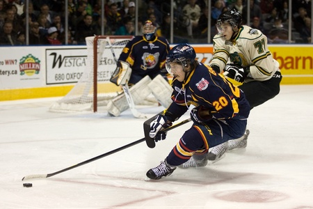 barrie: London Ontario, Canada - November 25, 2011. Chris Buonomo (20) of the Barrie Colts turns to protect the puck from Josh Anderson (77) of the London Knights in a Ontario Hockey League game between the Barrie Colts and the London Knights. The visiting Barrie