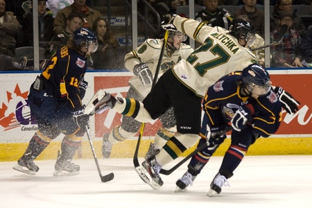 barrie: London Ontario, Canada - November 25, 2011. Brett Welychka (27) of the London Knights jumps to avoid a hip check in a Ontario Hockey League game between the Barrie Colts and the London Knights. The visiting Barrie Colts won the game 6-2. Editorial