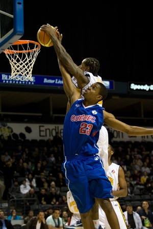 john labatt centre: London Ontario, Canada - November 17, 2011. Yannick Anzuluni (23) goes up for a basket but is blocked by Gabe Freeman of the London Lighting during a National Basketball League of Canada game between the London Lightning and Quebec Kebs. London won the ga Editorial