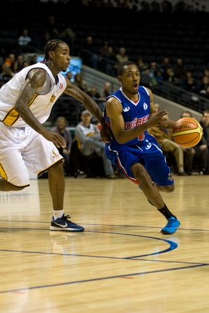 London Ontario, Canada - November 17, 2011. Royce Parran (12) of the Quebec Kebs carries the ball past Gabe Freeman (25) of the London Lightning during a National Basketball League of Canada game between the London Lightning and Quebec Kebs. London won th Editorial