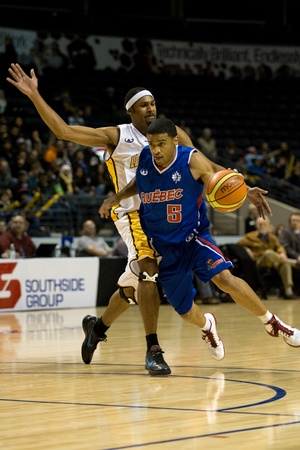 London Ontario, Canada - November 17, 2011. Tommy Mitchell (5) carries the ball past Rodney Buford of the London Lightning during a National Basketball League of Canada game between the London Lightning and Quebec Kebs. London won the game 85-79.