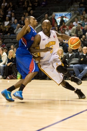 london lightning: London Ontario, Canada - November 17, 2011. DeAnthony Bowden of the London Lightning carries the ball around Tommy Mitchell of the Quebec Kebs during a National Basketball League of Canada game between the London Lightning and Quebec Kebs. London won the