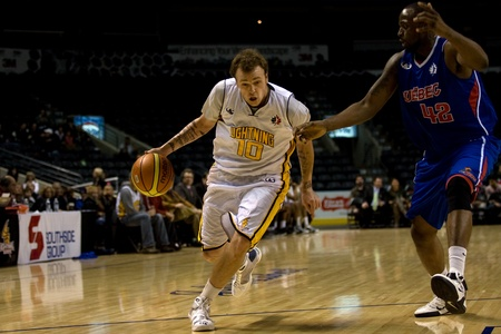 London Ontario, Canada - November 17, 2011. Taylor King (10) of the London Lightning looks for a way around Ricky Volcy (42) of the Quebec Kebs during a National Basketball League of Canada game between the London Lightning and Quebec Kebs. London won the