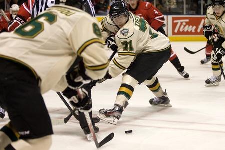 chris: Londres, Ontario, Canad� - 20 de noviembre de 2011: Chris Tierney (71) ha sufrido una confrontaci�n dirigiendo el disco de nuevo a Andreas Athanasiou durante un partido de Ontario Hockey League entre los Caballeros de Londres y el ataque de Owen Sound. Londres gan� el partido 3-2 en tiempo extra.