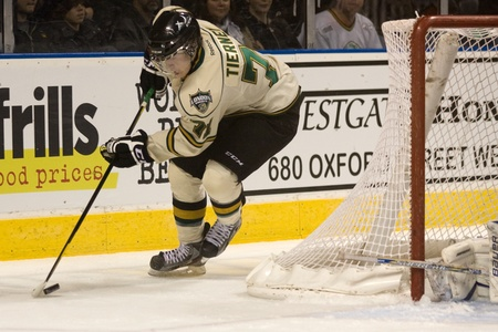 chris: London Ontario, Canada - November 20, 2011: Chris Tierney (71) carries the puck behind the Owen Sound Attack net during an Ontario Hockey League game between the London Knights and Owen Sound Attack. London won the game in overtime 3-2.