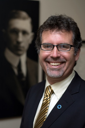 London Ontario, Canada - August 5, 2011. Grant Maltman, Curator at Banting House. He is photographed in front of a portrait of Dr. Frederick Banting's located inside Banting House in London Ontario Canada. It was inside this house that Dr. Frederick Banti Redactioneel