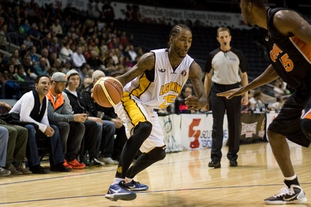 london lightning: London Ontario, Canada - December 10, 2011. Gabe Freeman (25) looks for a lane to the basket against David Collins (55) in a National Basketball League of Canada game between the Oshawa Power and the London Lightning. The visiting Oshawa Power handed Lond Editorial