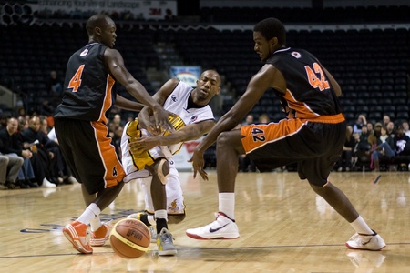 London Ontario, Canada - December 10, 2011. Tim Ellis, centre, makes a pass between Tut Ruach (4) and Omari Johnson (42) in a National Basketball League of Canada game between the Oshawa Power and the London Lightning. The visiting Oshawa Power handed Lon Редакционное