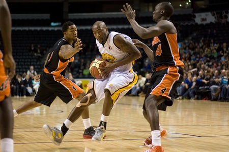 London Ontario, Canada - December 10, 2011. Tim Ellis, centre drives between Marcus Johnson (1) and Tut Ruach (4) in a National Basketball League of Canada game between the Oshawa Power and the London Lightning. The visiting Oshawa Power handed London the Редакционное