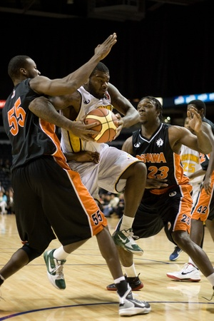 john labatt centre: London Ontario, Canada - December 10, 2011. Shamari Spears (35) drives between David Collins (55) and Jerome Brown (23) in a National Basketball League of Canada game between the Oshawa Power and the London Lightning. The visiting Oshawa Power handed Lond Editorial